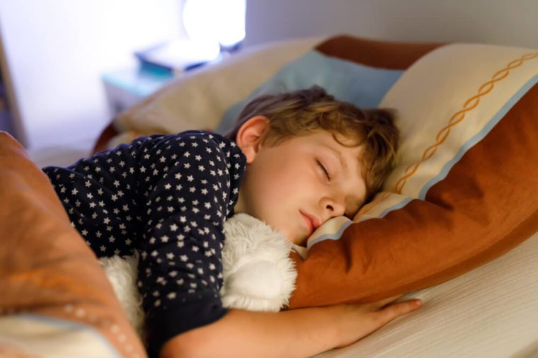Little preschool kid boy sleeping in bed with colorful lamp. School child dreaming and holding plush toy. Kid angry of darkness.
