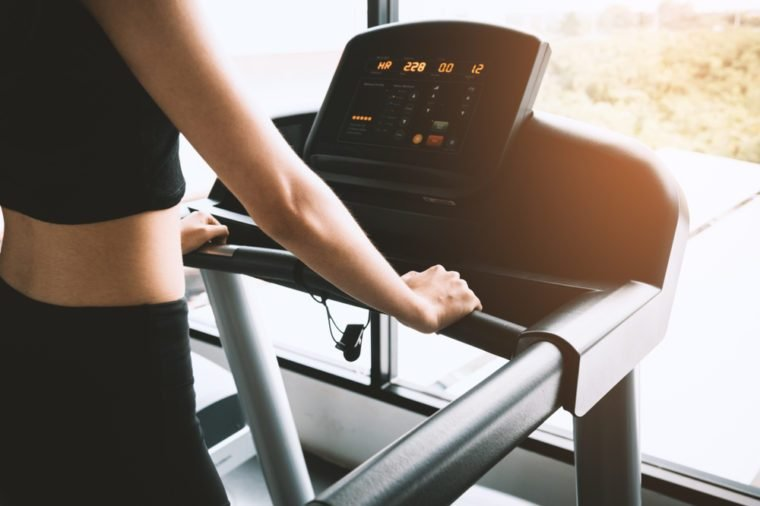 Asian sport woman walking or running on treadmill equipment in fitness workout gym. Sport and Beauty concept. Workout and Strength Training theme. Cardio and Diet theme
