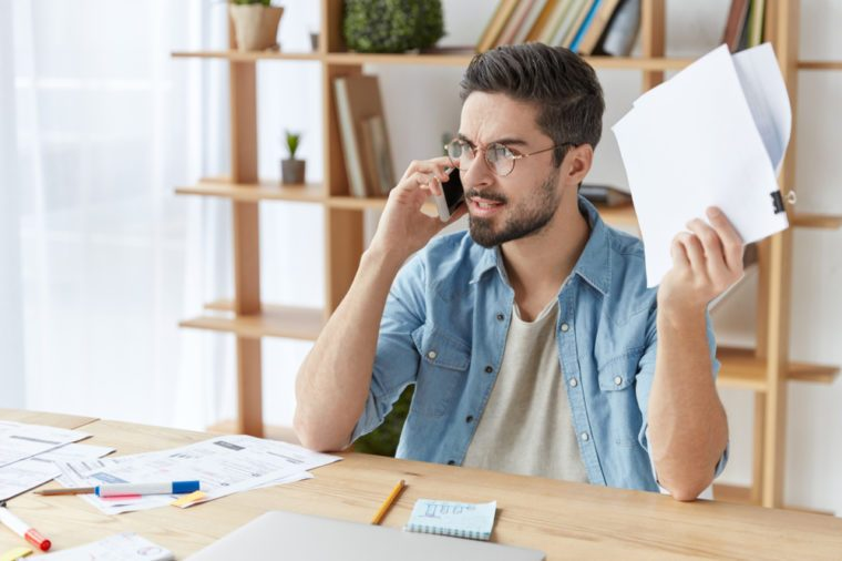 Shot of serious angry male enterpreneur tries to prove his rightness, has qaurrel with boss over smart phone, holds papers, solve company`s problems together. Annoyed boss shouts at colleague