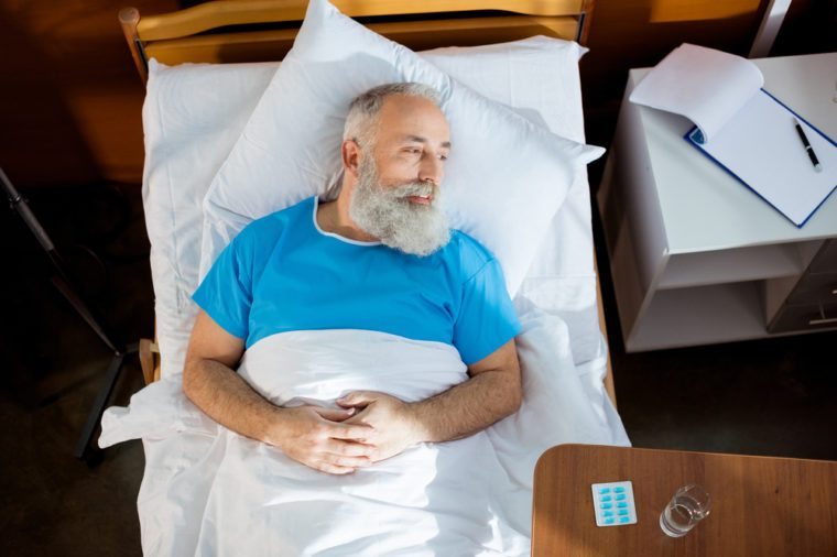 Top view of senior bearded man lying in hospital bed and lookig at distance