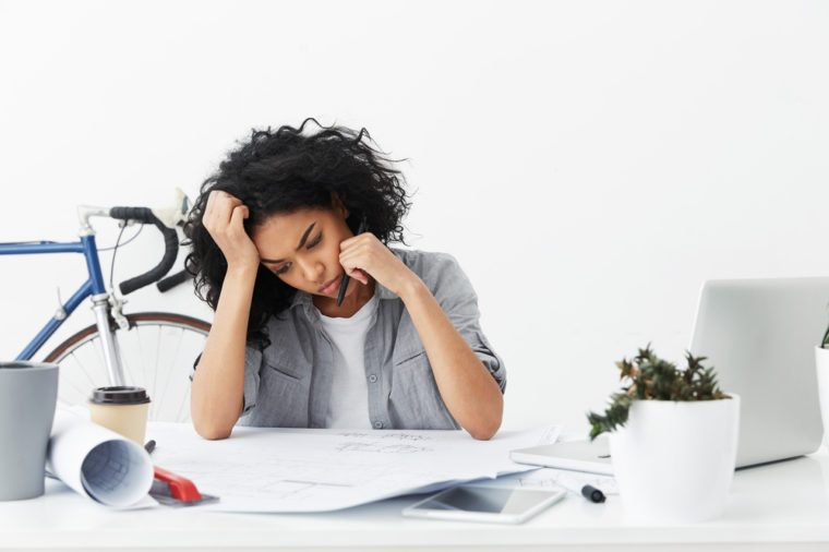 Portrait of bored and tired Afro American female architect working on architectural plan unwillingly, feeling indifference, sitting at white office desk with blueprints and electronic devices