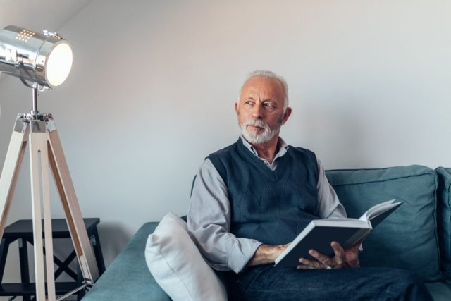 Elderly man reading a book on the sofa