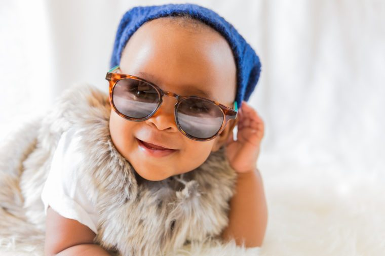 Super cool baby. Hipster baby in fur vest and sunglasses lies on a white bed in a room with curtains. Baby smiles while putting on sunglasses.