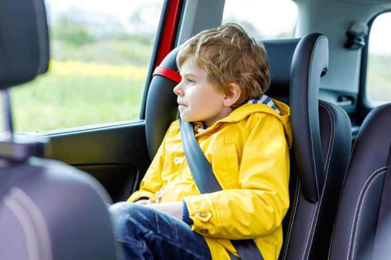 Adorable cute preschool kid boy sitting in car in yellow rain coat. Little school child in safety car seat with belt enjoying trip and journey. Safe travel with kids and traffic laws concept.