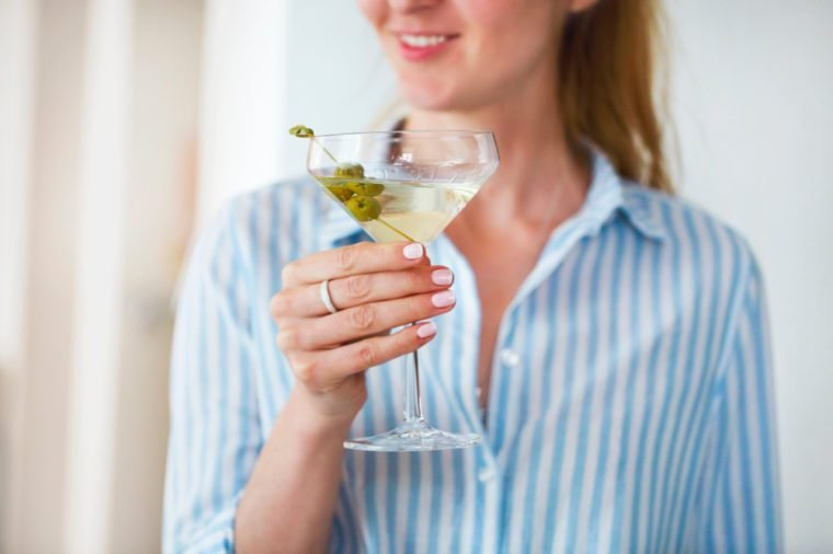 Woman holding glass with martini and green olives, focus on olives