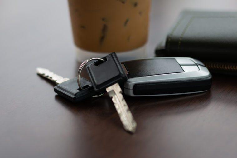 Abstract Holiday travel vacations with Car Keys and Wallet on the Wooden Table in Coffee Shop.