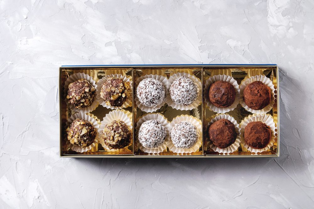 Variety of homemade dark chocolate truffles with cocoa powder, coconut, walnuts in golden gift box over gray texture background. Top view, copy space.