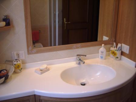 Mobile bagno con piano sagomato e lavello in corian