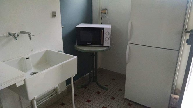 A microwave and refrigerator in the womens' restroom.