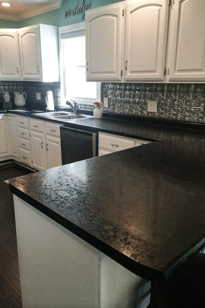 painted white cabinets with faux tin backsplash and black hd countertops
