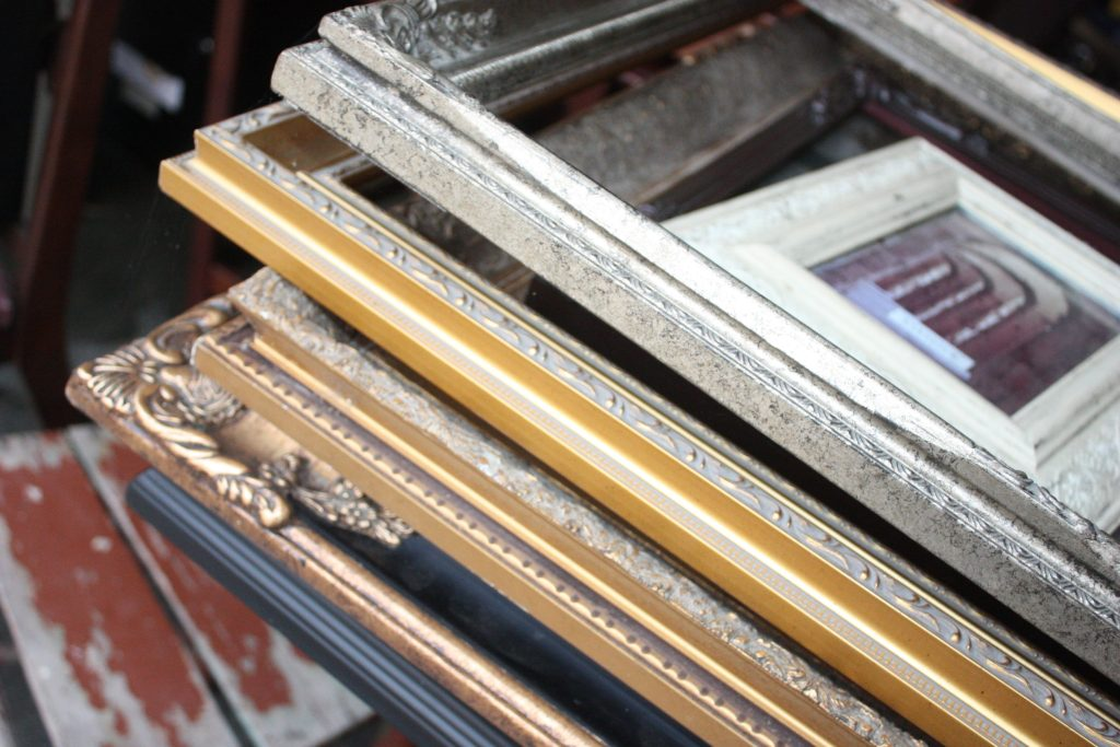 Large stack of old and new picture frames of all sizes.