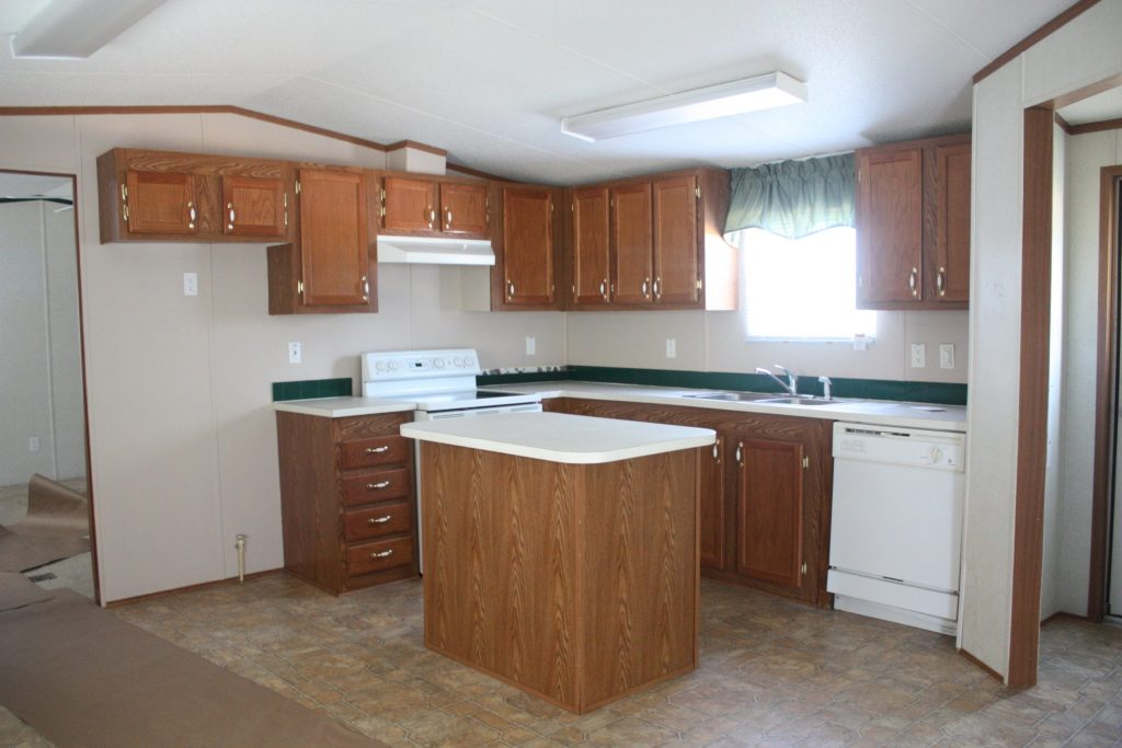 This mobile home kitchen needed major updating, and boy did it get it! Check out the post for the cabinet makeover - and how the backsplash was only $40!