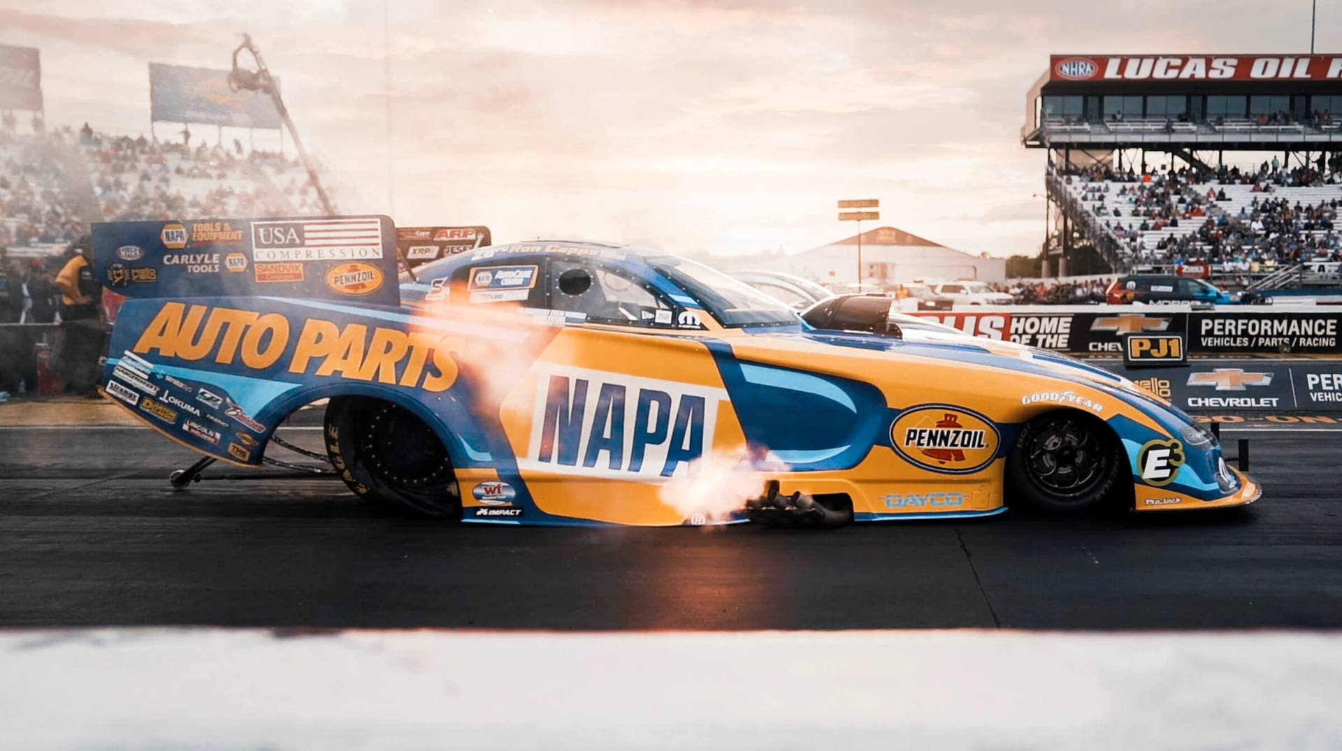 Ron Capps launches the NAPA Dodge at dusk at the 2019 NHRA U.S. Nationals.