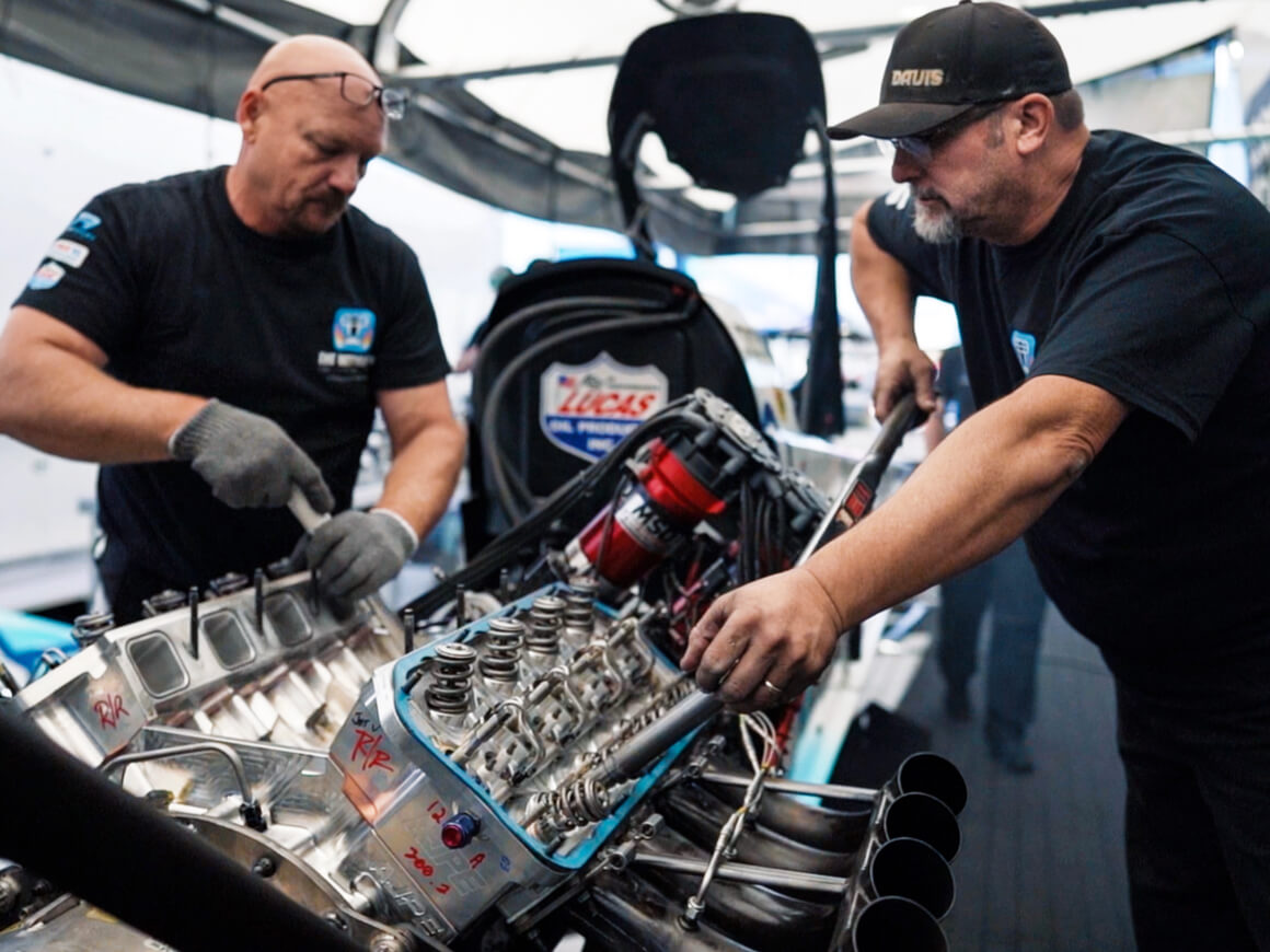 Crew members on Justin Ashley's NHRA Top Fuel Dragster service an engine at the conclusion of day one of qualifying at the 2019 NHRA World Finals.