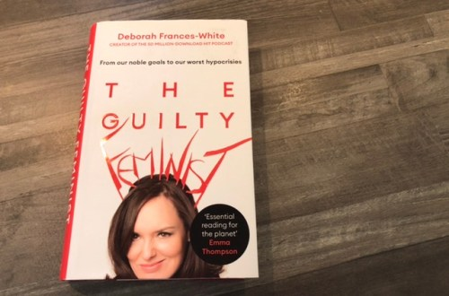 A book titled The Guilty Feminist by Deborah Frances-White, on a wooden background