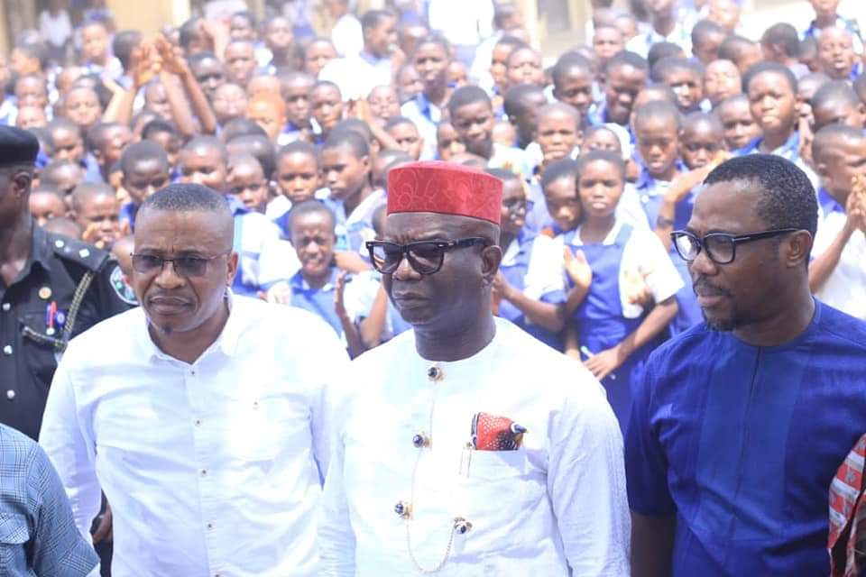 Chairman of the Committee flanked by some members of the committee at Secondary School Etoi, with students watching with admiration