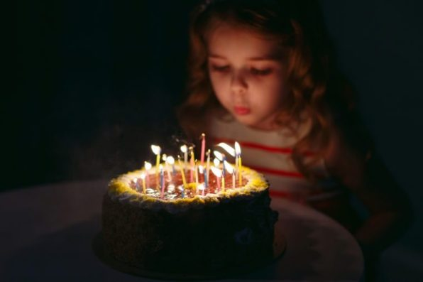 Little girl blowing out her birthday candles