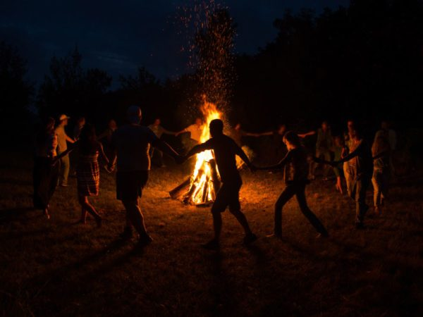 Group dance around giant bonfire