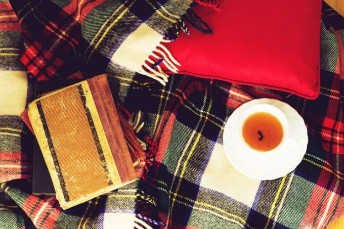Plaid blanket with a cup of tea and notebook
