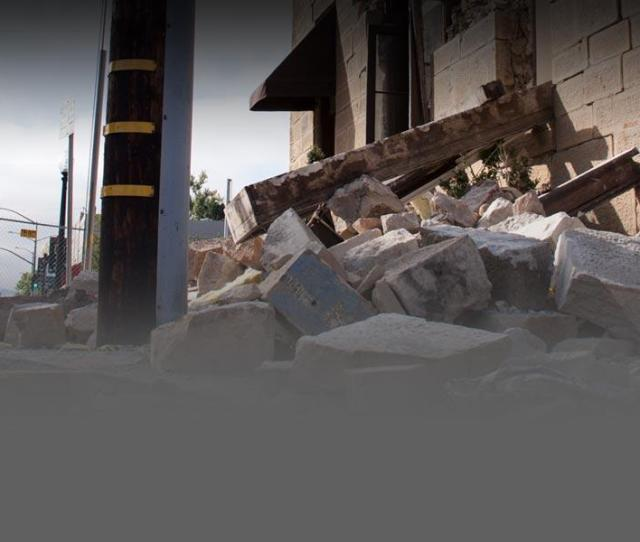 Photo Of Rubble And Debris On The Ground Next To A Damaged Building That Sustained Structural