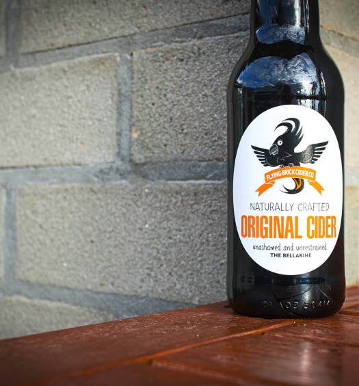 Flying Brick Original Cider bottle against a brick wall