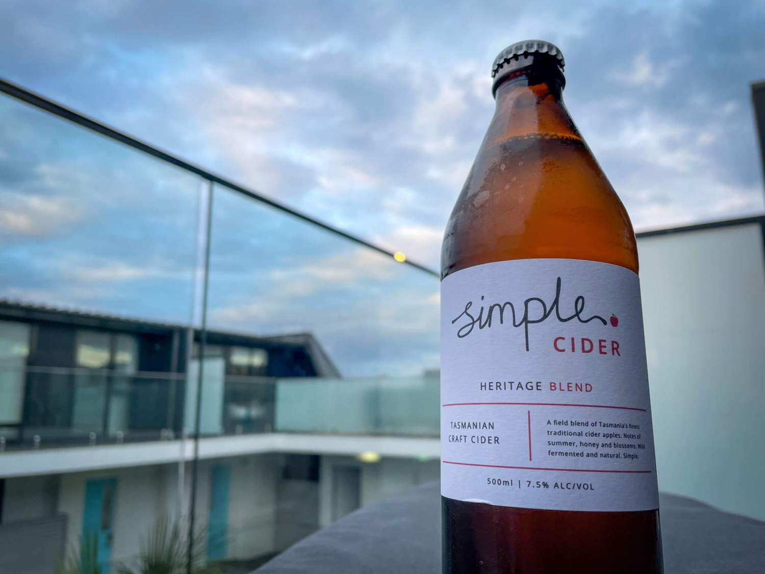 a bottle of Simple Cider Heritage Blend with city skyline in the background