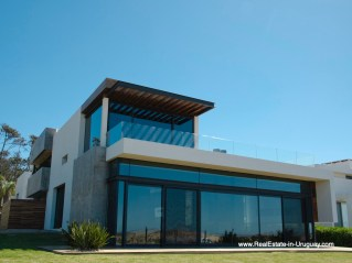 Front of Modern High-Tech Home in Laguna Blanca by Manantiales
