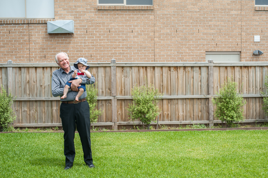 Grandfather and grandson standing in backyard