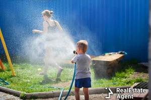 Young kid sprinkling water on woman in Hungary during Easter festivities