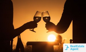 Two wine glasses toasting each other with the sunset on the background on a romantic getaway