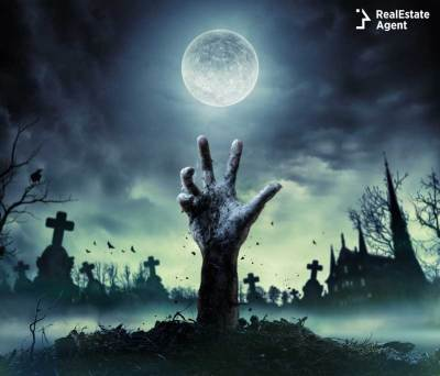 horror movie image from a cemetery with a zombie hand getting outside from ground