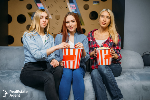3 teenage girls siting on a couch and enjoying popcorn while talking