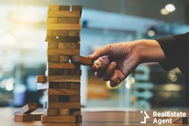hand of businessman pulling out a wooden block