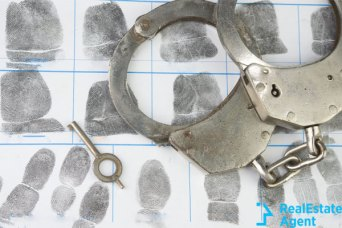 Handcuffs and key on top of fingerprints sheet