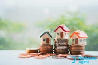 Miniature homes on top of rolls of change concept image.