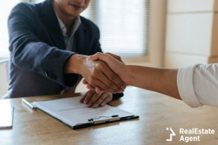 Real estate agents shacking hands with client.