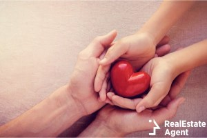 adult and child hands holding red heart