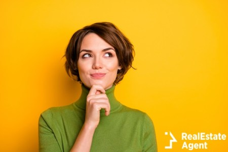 Pensive woman standing against yellow background
