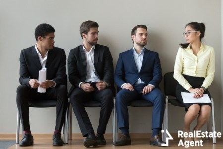 Diverse male applicants looking at woman