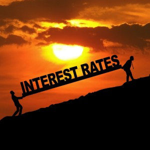 Silhouette of businessmen carrying Interest Rates word uphill