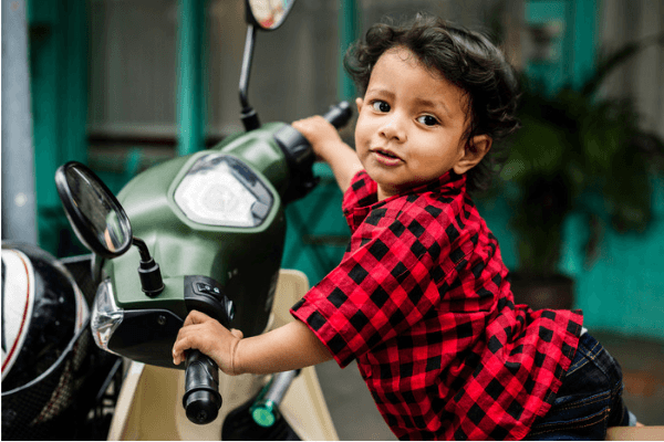 modern Hindu baby boy Indian on motorcycle