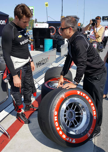 Will Power and Race Engineer David Faustino analyze a set of used Firestone Red's after morning warm-ups