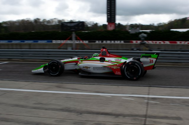 Pato O'Ward drives down pit lane during practice