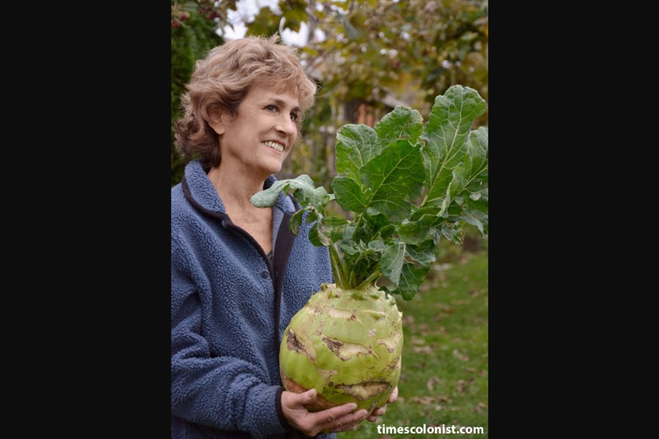 Barbara Damrosch holds a giant kohlrabi in her garden
