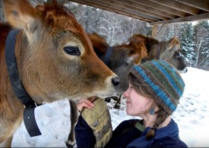 Caitlin Frame nuzzles a cow in her winter hat outside at the Real Organic certified farm Milkhouse Maine