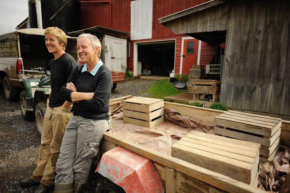 Debra Brubaker and Hannah Smith-Brubaker lean on lumber at Village Acres Farm in Mifflintown, Pennsylvania