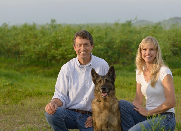 Hugh and Lisa Kent and their dog look at the camera wearing white shirts and denim pants. Rows of blueberries and sky are behind them.