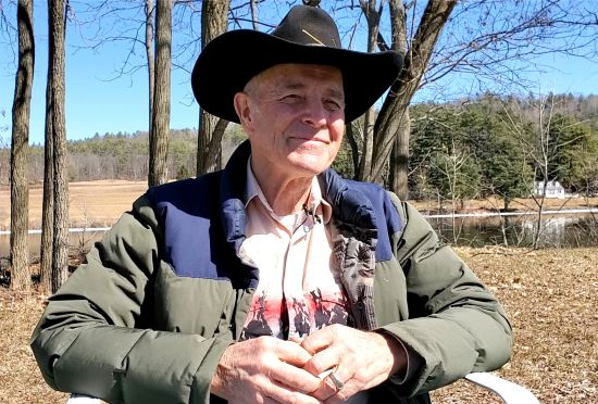 An older man in a black cowboy hat sits outside against a blue sky and trees with hands folded and he is smiling.
