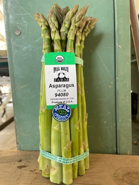 "A green bunch of asparagus with a plastic label reading ""Full Belly Farm Asparagus. Product of the U.S.A. Real Organic Project"""