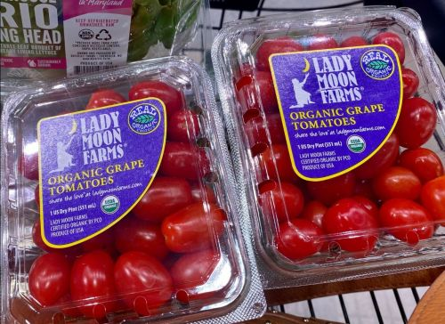 A photo of two plastic containers filled with small red cherry tomatoes with a label for Lady Moon Farms